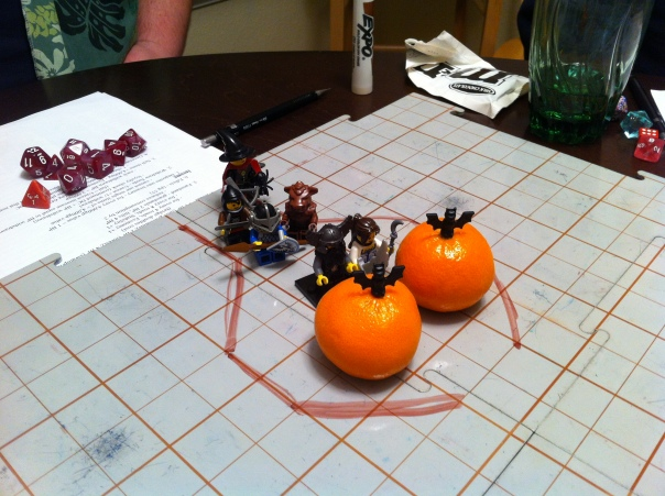 Lego figures stand in for roleplaying characters; tangerines stand in for clouds of bats.